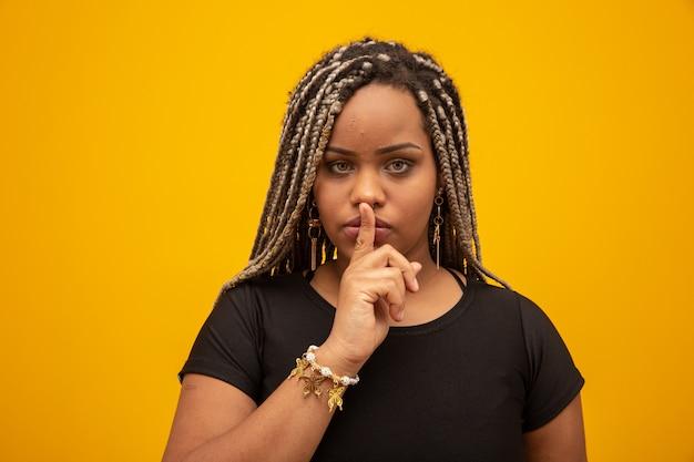 Giovane donna afro-americana che segnala silenzio. ragazza con il dito in bocca per chiedere silenzio.