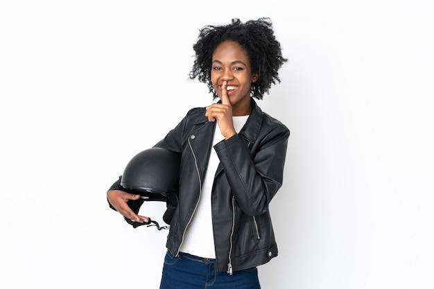 Giovane donna afro-americana con un casco da motociclista sul muro bianco facendo il gesto del silenzio