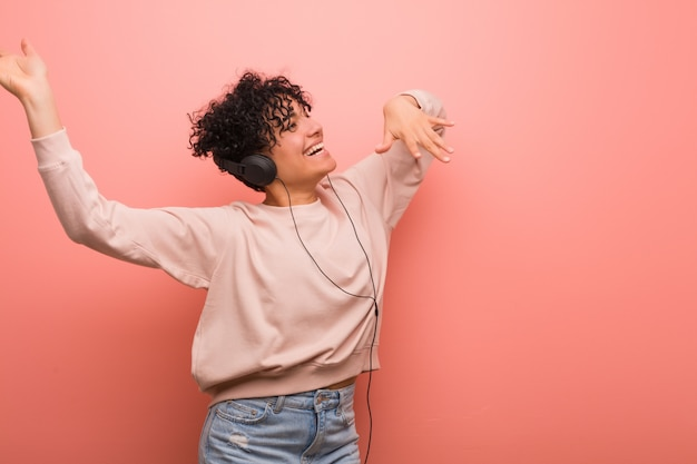 Giovane donna afro-americana con una voglia che balla e ascolta la musica con una cuffia
