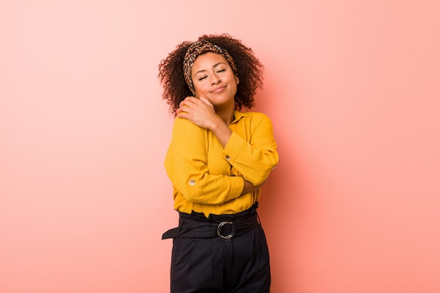 Giovane donna afro-americana contro un abbracci rosa, sorridente spensierato e felice.