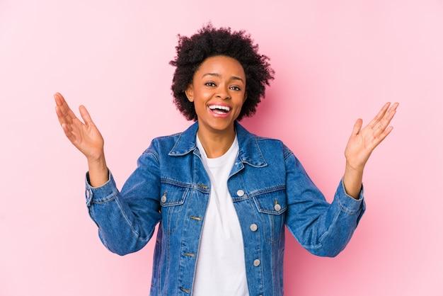 Giovane donna afro-americana contro un muro rosa che riceve una piacevole sorpresa, eccitata e alzando le mani.