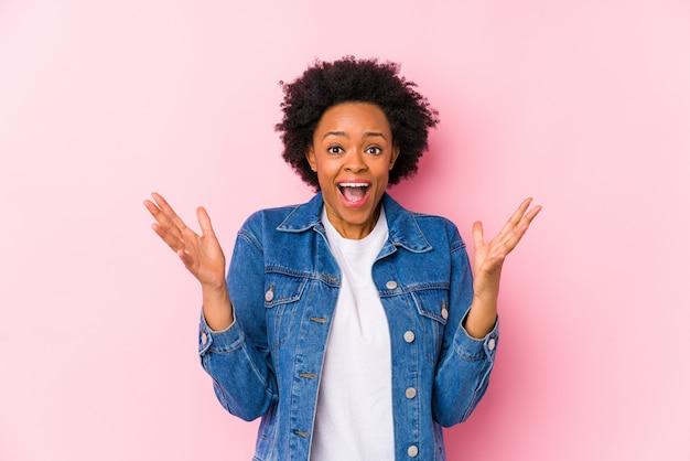 Giovane donna afro-americana contro un muro rosa isolato per celebrare una vittoria o un successo, è sorpreso e scioccato.