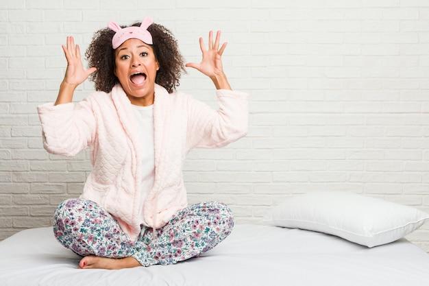 Giovane donna afro-americana nel letto che indossa un pigiama che celebra una vittoria o un successo, è sorpreso e scioccato.