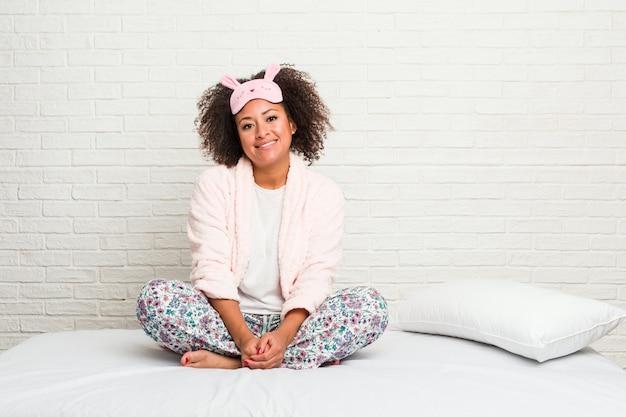 Giovane donna afro-americana nel letto indossando pijama felice, sorridente e allegro.