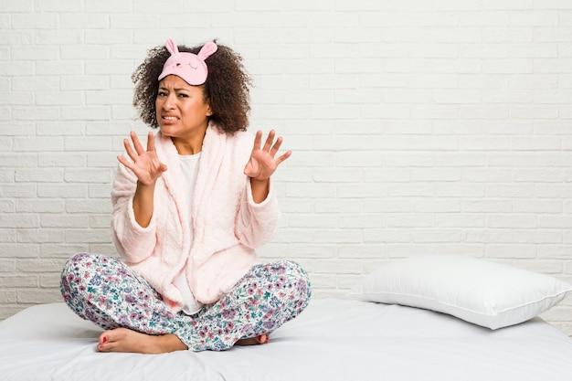 Giovane donna afro-americana nel letto indossando pijama rifiutando qualcuno che mostra un gesto di disgusto.