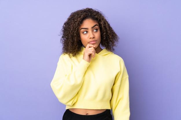Giovane donna afro-americana sul muro con dubbi e con espressione del viso confuso