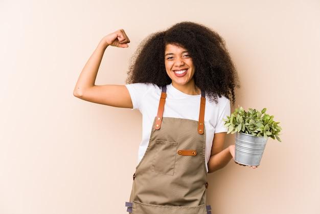 Giovane donna afro del giardiniere che tiene un pugno isolante della pianta dopo una vittoria, concetto del vincitore.