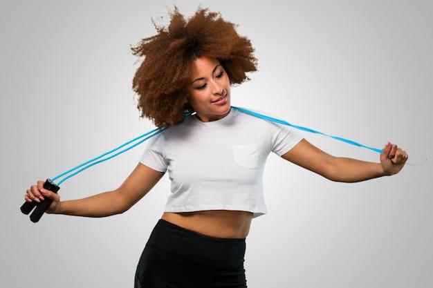 Giovane donna afro fitness con un salto corda