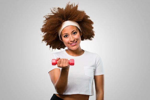 Giovane donna afro fitness esercitando con manubri
