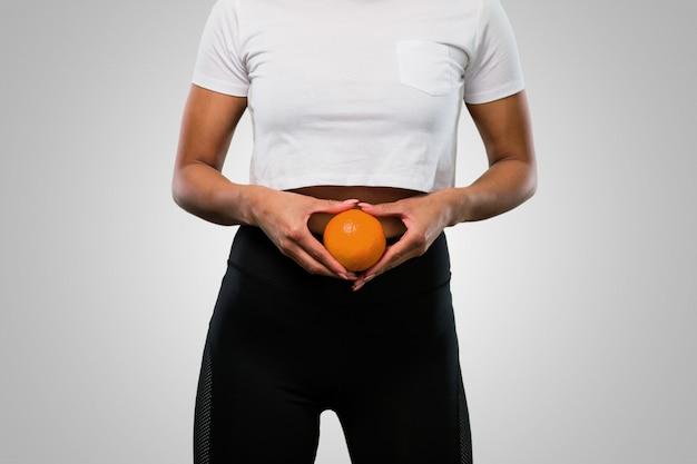 Giovane donna afro fitness in possesso di un arancio
