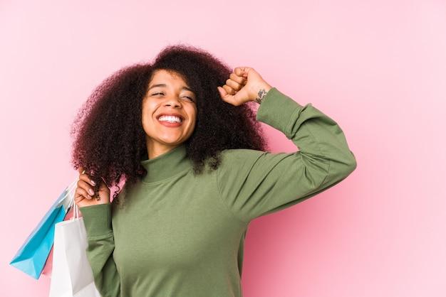 Giovane donna afro shopping giovane donna afro acquisto isolayoung donna afro in possesso di un pugno di rose isolato alzando il pugno dopo una vittoria, concetto vincitore. <mixto>