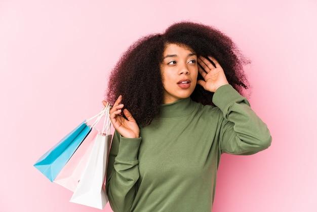 Giovane donna afro shopping isolato giovane donna afro acquisto isolayoung donna afro in possesso di un isolato rose cercando di ascoltare un gossip. <mixto>