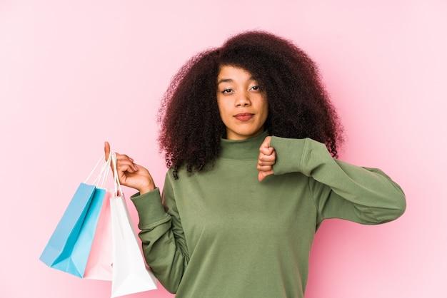 Giovane donna afro shopping isolato giovane donna afro acquisto isolayoung donna afro in possesso di un isolato rose mostrando un gesto antipatia, pollice verso il basso.