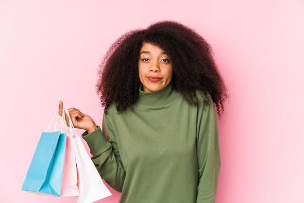 Giovane donna afro shopping isolato giovane donna afro acquisto isolayoung donna afro in possesso di un isolato rose scrollate di spalle le spalle e gli occhi aperti confusi. <mixto>