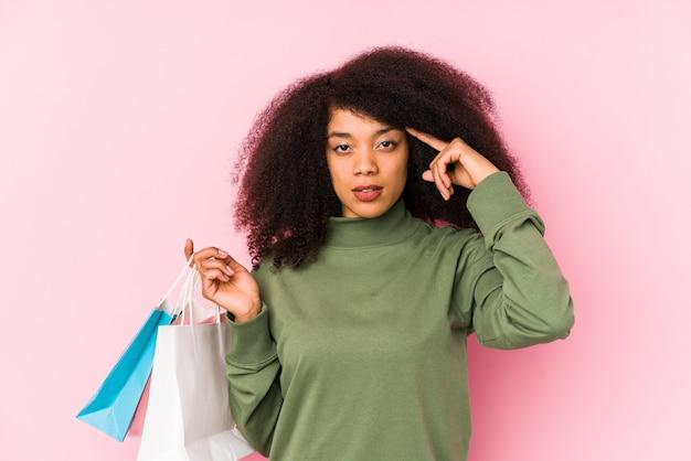 Giovane donna afro shopping isolato giovane donna afro acquisto isolayoung donna afro in possesso di un tempio di puntamento isolato di rose con dito, pensando, focalizzato su un compito. <mixto>