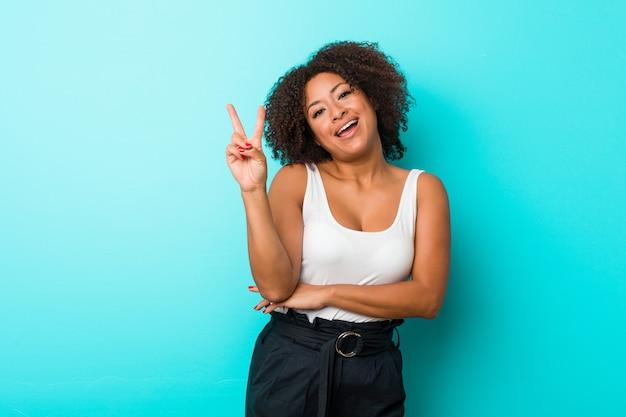 Giovane donna afroamericana allegra e spensierata che mostra un simbolo di pace con le dita.