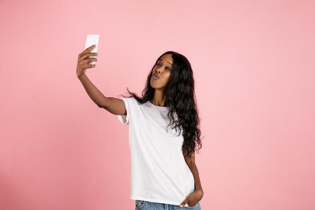 Giovane donna afroamericana allegra isolata su spazio di corallo, emozionale ed espressivo