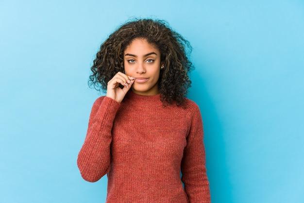 Giovane donna afroamericana capelli ricci con le dita sulle labbra mantenendo un segreto.