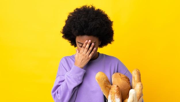 Giovane donna afroamericana che compra qualcosa di pane isolato su fondo giallo con l'espressione stanca e malata