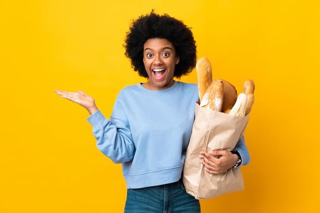 Giovane donna afroamericana che compra qualcosa di pane isolato su giallo con espressione facciale colpita