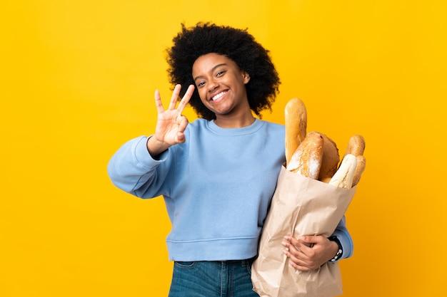 Giovane donna afroamericana che compra qualcosa di pane isolato sulla parete gialla felice e che conta tre con le dita