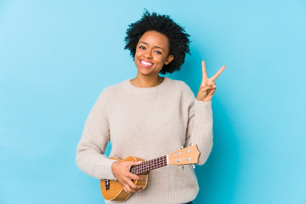 Giovane donna afroamericana che gioca ukelele allegro e spensierato mostrando un simbolo di pace con le dita.