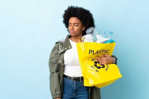 Giovane donna afroamericana che giudica una borsa di riciclaggio isolata su variopinto avendo dubbi mentre osservando lato