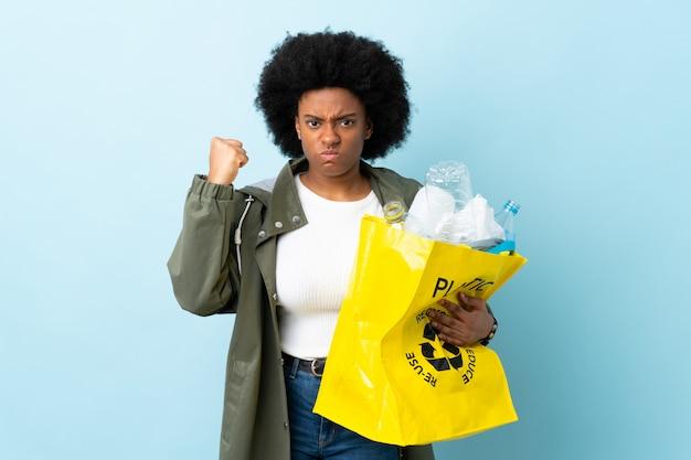 Giovane donna afroamericana che giudica una borsa di riciclaggio isolata su variopinto con l'espressione infelice