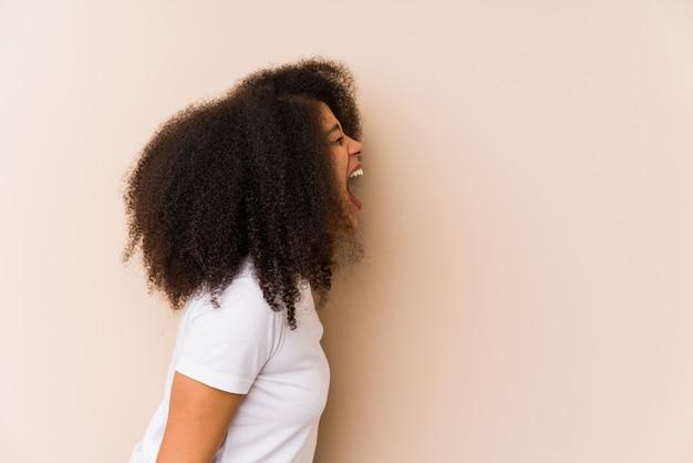 Giovane donna afroamericana che grida verso uno spazio della copia
