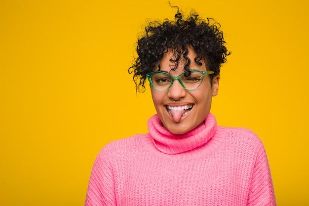 Giovane donna afroamericana che indossa un maglione rosa divertente e amichevole che attacca fuori lingua.