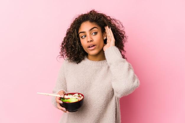 Giovane donna afroamericana che mangia le tagliatelle che provano ad ascoltare un gossip.