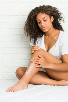 Giovane donna afroamericana che ottiene crema idratante sulle sue gambe
