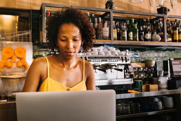 Giovane donna afroamericana che per mezzo del computer portatile al caf�