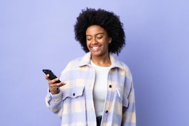 Giovane donna afroamericana che per mezzo del telefono cellulare sulla parete porpora con l'espressione felice