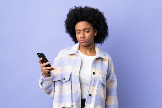 Giovane donna afroamericana che per mezzo del telefono cellulare sulla parete porpora con l'espressione triste