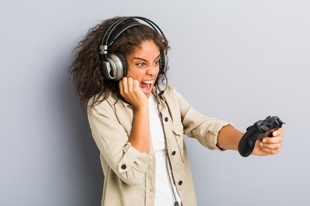 Giovane donna afroamericana che per mezzo delle cuffie e del controller di gioco