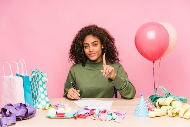 Giovane donna afroamericana che progetta un compleanno che mostra numero uno con il dito.