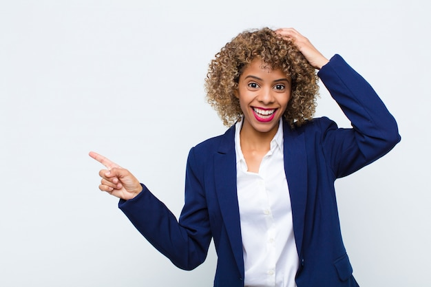 Giovane donna afroamericana che ride, che sembra felice, positiva e sorpresa, realizzando una grande idea che punta allo spazio laterale della copia contro la parete piana
