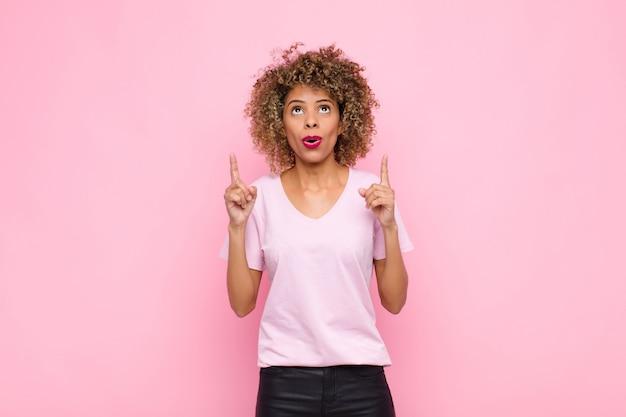 Giovane donna afroamericana che si sente intimorita e con la bocca aperta rivolta verso l'alto con uno sguardo scioccato e sorpreso sul muro rosa