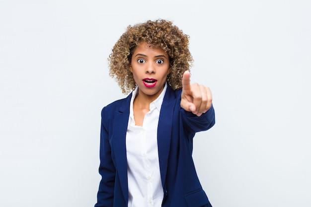 Giovane donna afroamericana che si sente scioccata e sorpresa, indicando e guardando in soggezione con sguardo stupito e a bocca aperta sulla parete piatta