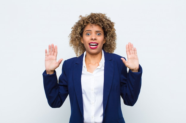 Giovane donna afroamericana che si sente stupefatta e spaventata, temendo qualcosa di spaventoso, con le mani aperte davanti dicendo di stare lontano sulla parete piatta