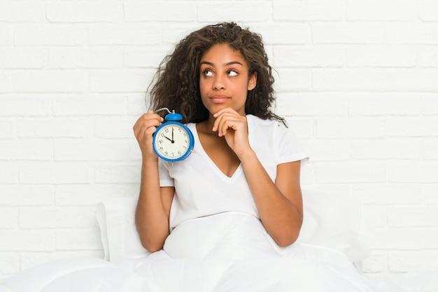 Giovane donna afroamericana che si siede sul letto che tiene una sveglia che osserva obliquamente con espressione dubbiosa e scettica.