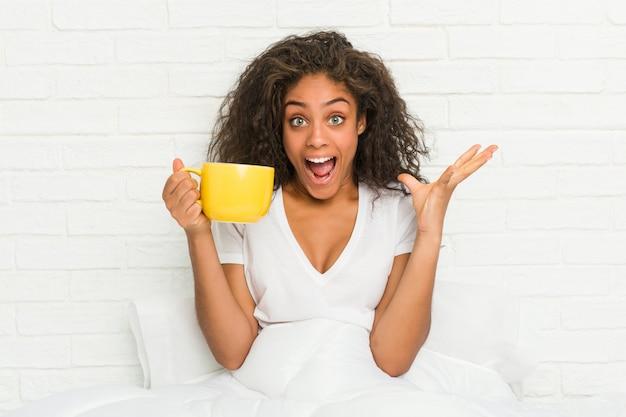 Giovane donna afroamericana che si siede sul letto che tiene una tazza da caffè che celebra una vittoria o un successo