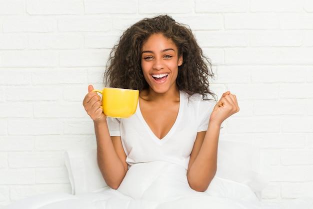 Giovane donna afroamericana che si siede sul letto che tiene una tazza da caffè che incoraggia spensierata ed eccitata. concetto di vittoria.