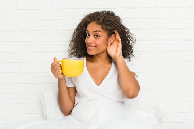 Giovane donna afroamericana che si siede sul letto che tiene una tazza da caffè che prova ad ascoltare un gossip.