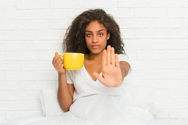Giovane donna afroamericana che si siede sul letto che tiene una tazza da caffè che sta con il fanale di arresto di rappresentazione della mano tesa