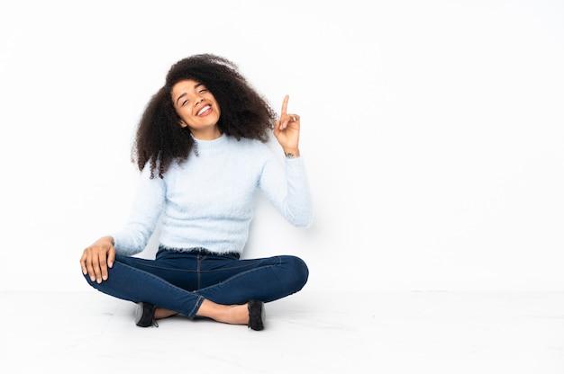 Giovane donna afroamericana che si siede sul pavimento che mostra e che solleva un dito nel segno del meglio