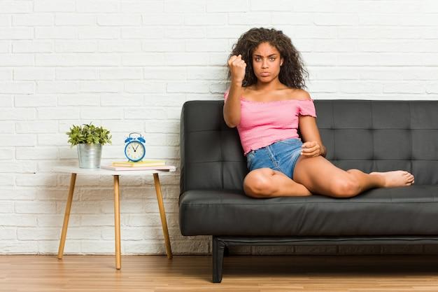 Giovane donna afroamericana che si siede sul sofà che mostra pugno con espressione facciale aggressiva.