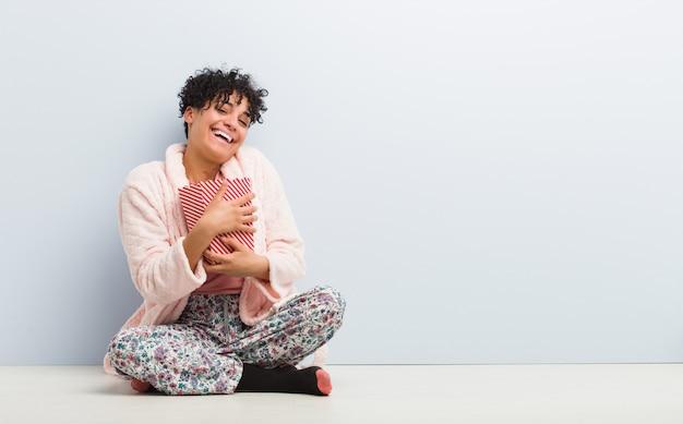 Giovane donna afroamericana che si siede tenendo un contenitore di popcorn