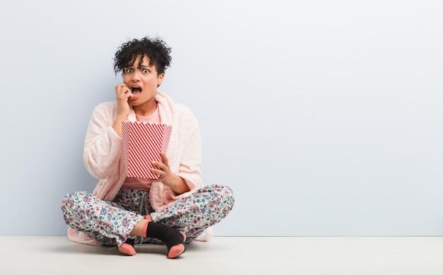 Giovane donna afroamericana che tiene le unghie mordaci di un secchio del popcorn, nervose e molto ansiose.